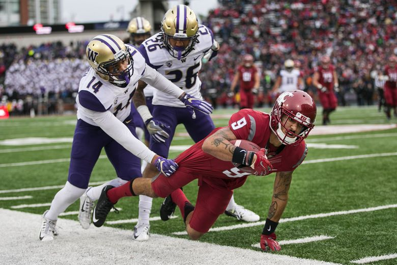 Washington State Cougars wide receiver Gabe Marks (9) catches the ball for a 15-yard gain in the third quarter while being defended by Washington Huskies defensive back Jojo McIntosh (14)and Washington Huskies defensive back Sidney Jones (26). Marks caught a touchdown pass on the next play. (Johnny Andrews / The Seattle Times)