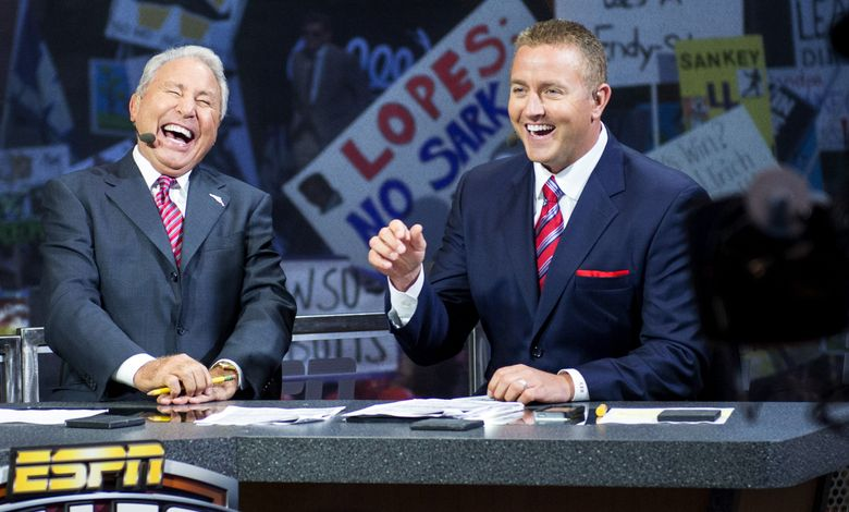 Hosts Lee Corso and Kirk Herbstreit share a laugh as they talk during ESPN's 'College GameDay' broadcast at the University of Washington early Saturday morning, Oct. 12, 2013. This is the first stop in Seattle for the popular program. (Seattle Times file)
