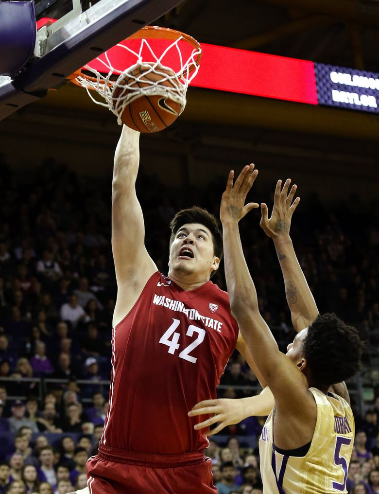 Washington State center Conor Clifford (42) dunks over Washington's Dejounte Murray in a March 2 game in Seattle. Clifford and Cougars coach Ernie Kent have formed a close bond. (Elaine Thompson/AP)