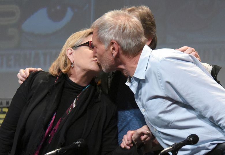 """FILE – In this July 10, 2015, file photo, Carrie Fisher, left, and Harrison Ford kiss at the Lucasfilm's """"Star Wars: The Force Awakens"""" panel on day 2 of Comic-Con International in San Diego, Calif. Fisher revealed in an interview with People magazine published online on Nov. 15, 2016, that she had an affair with Ford during the filming of the 1977 film, """"Star Wars."""" (Photo by Richard Shotwell/Invision/AP, File)"""