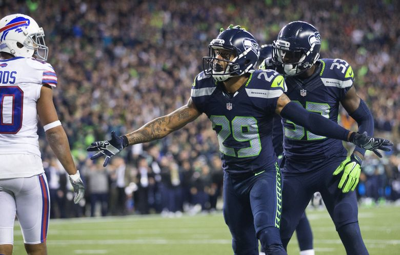 Seattle Seahawks free safety Earl Thomas (29) is patted on the head by Seattle Seahawks strong safety Kelcie McCray (33) after breaking up a pass for Buffalo Bills wide receiver Robert Woods to turn over the ball and give the Seahawks the game. (Lindsey Wasson/The Seattle Times)