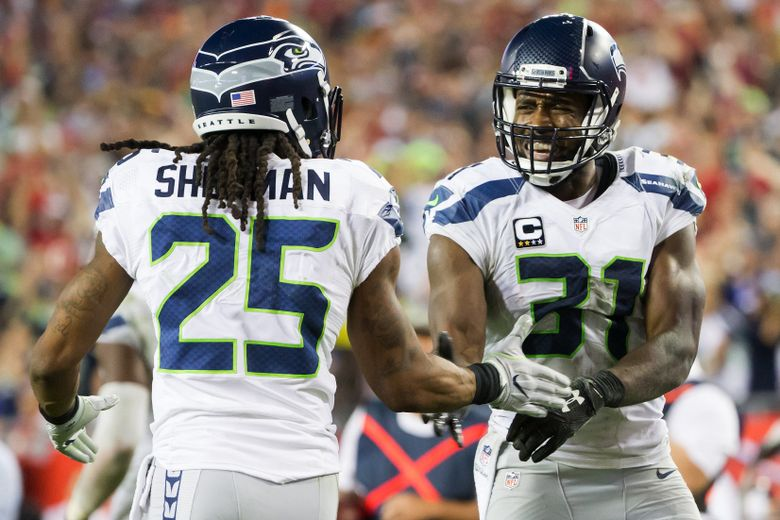Seahawks cornerback Richard Sherman congratulates strong safety Kam Chancellor on his interception in the fourth quarter as the Seattle Seahawks take on the Tampa Bay Buccaneers at Raymond James Stadium in Tampa Sunday, November 27, 2016 — 0438807858 (Bettina Hansen/The Seattle Times)