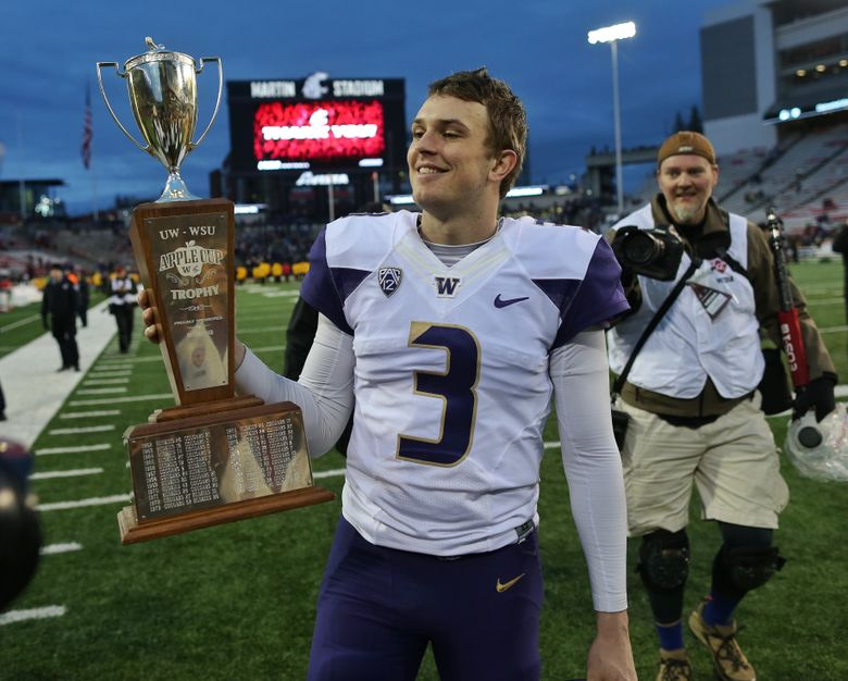 Huskies quarterback Jake Browning holds the Apple Cup trophy after their win.   The Washington Huskies faced off against the Washington State Cougars in the Apple Cup on Friday, November, 25, 2016, in Pullman.