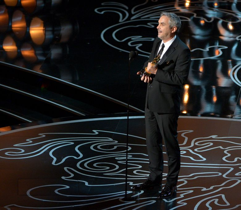 """FILE – In this March 2, 2014, file photo, Alfonso Cuaron accepts the award for best director of the year for """"Gravity"""" during the Oscars at the Dolby Theatre in Los Angeles. The film crew for Cuaron's latest picture has been involved in an altercation on a downtown Mexico city street. The Mexico City police department said Wednesday, Nov. 2, 2016, that a group of people approached the crew and identified themselves as borough code inspectors. The department said """"after an exchange of words, there was an altercation, with no injuries reported."""" (Photo by John Shearer/Invision/AP, File)"""