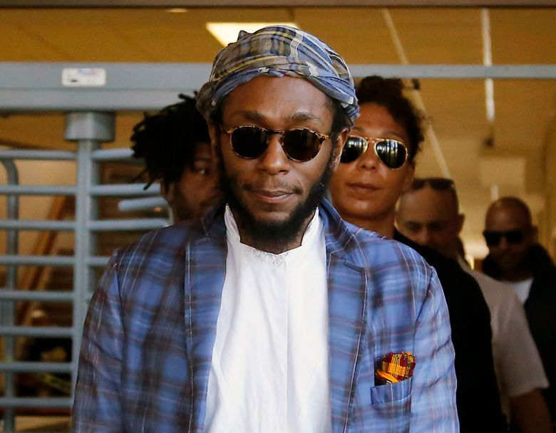 FILE – In this March 24, 2016 file photo, American actor and musician Yasiin Bey, also known as Mos Def, leaves the Bellville Magistrates' Court in Bellville, South Africa. Bey, who announced he was retiring from the music business after getting into a legal fight in South Africa, will take the stage at the Apollo Theater on Dec. 21 and then play the Kennedy Center from Dec. 31-Jan. 2. The 42-year-old rapper and actor was charged with trying to leave South Africa while using a passport not recognized by that country. (AP Photo/Schalk van Zuydam, File)