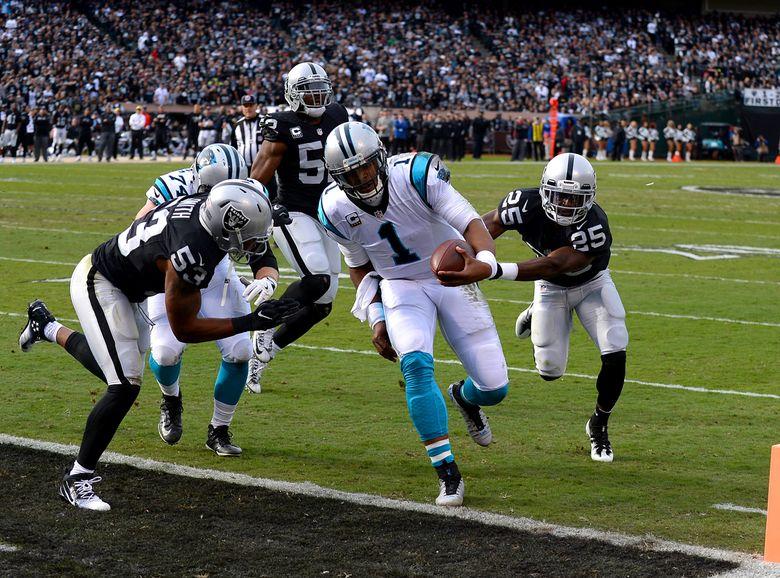 Carolina Panthers quarterback Cam Newton, center, rushes for a touchdown against the Oakland Raiders during first-quarter action on Sunday. (Jeff Siner/TNS)