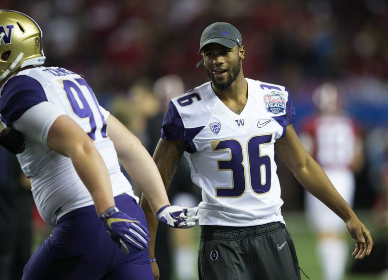 Washington Huskies linebacker Azeem Victor (36), out with a broken leg, greets teammates in the Georgia Dome in Atlanta in 2016. (Lindsey Wasson / The Seattle Times)