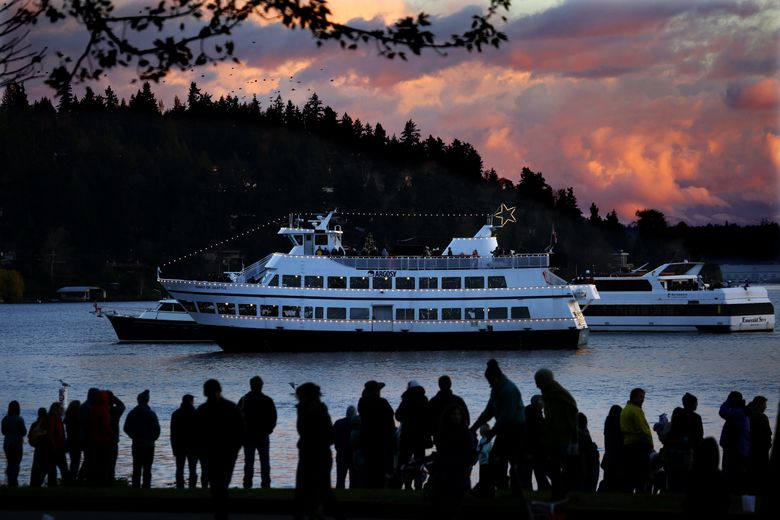 """At sunset early this month, a crowd at Seward Park in Seattle watches the """"Spirit of Seattle,"""" equipped with its own tree for the Argosy Cruises Christmas Ship Festival, and listens to the Rainier Youth Choirs as music is broadcast from loudspeakers to shore.  (Ken Lambert/The Seattle Times)"""