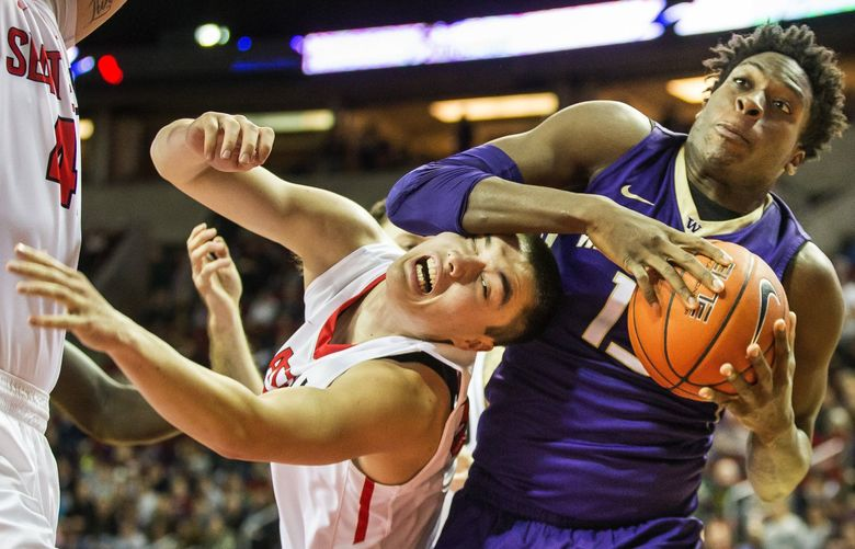 Washington's Noah Dickerson grabs the offensive board over Seattle University's Zack Moore in the first half.  The University of Washington men's basketball team played Seattle University at KeyArena in Seattle, Thursday, December 22, 2016.