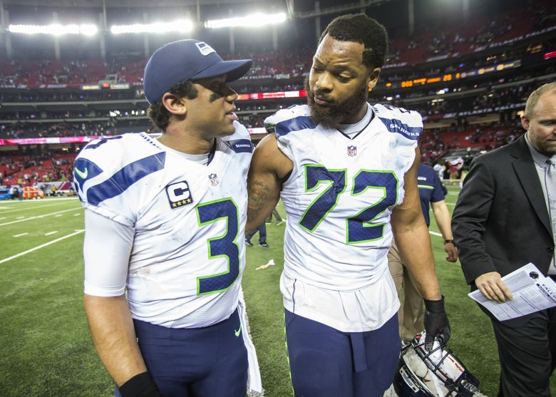 Michael Bennett puts his arm around Russell Wilson as the Seahawks exit the field following their 36-20 loss to Atlanta Saturday.   (Dean Rutz / The Seattle Times)