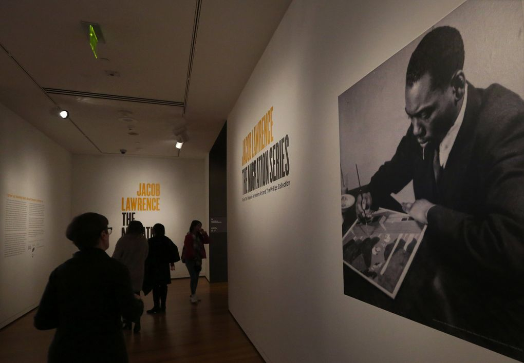 """A 1941 photograph of Jacob Lawrence by Kenneth F. Space welcomes visitors to his """"Migration Series,"""" 60 panels on display at the Seattle Art Museum through April 23. (Alan Berner / The Seattle Times)"""