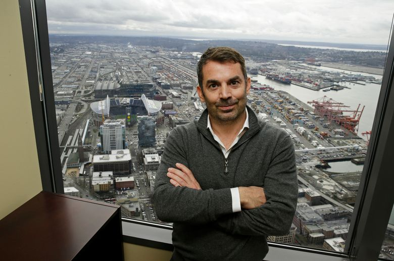 Chris Hansen, the investor hoping to build an arena to house a possible NBA basketball or NHL hockey franchise in Seattle's stadium district, poses for a photo in front of a window showing CenturyLink Field and Safeco Field on Thursday, Feb. 16, 2017, in downtown Seattle. (Ted S. Warren/AP)