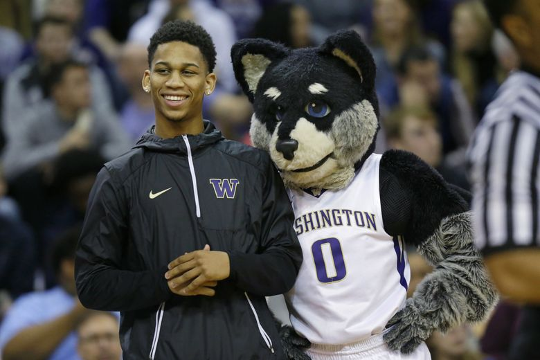 Blake Harris, a senior high school point guard from the Word of God Christian Academy in Raleigh, North Carolina, is introduced next to Harry the Washington mascot during a timeout in an NCAA college basketball game between Washington and Utah, Saturday, Jan. 21, 2017, in Seattle. (Ted S. Warren / AP)