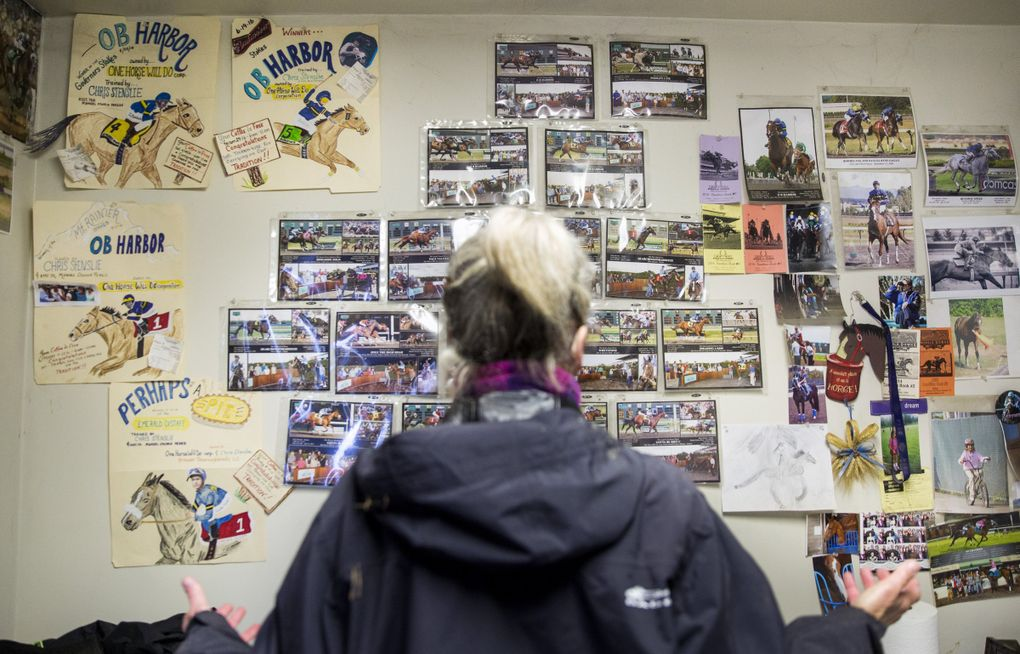 """Jody Peetz has a wall of images of successes and heartbreaks in her office at Emerald Downs in Auburn. Peetz had both last year when her horse O B Harbor had a wonderfully successful season, but was later found dead in his stable from a twisted intestine. Peetz works with trainer Chris Stenslie to manage her stable, """"One Horse Will Do."""" (Bettina Hansen / The Seattle Times)"""