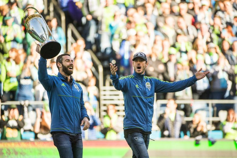 Zach Scott, left, and Brad Evans bring the MLS Cup onto the field before the team's home opener against New York in March. Evans has been injured much of the season until being used sparingly in recent games. (Dean Rutz/The Seattle Times)