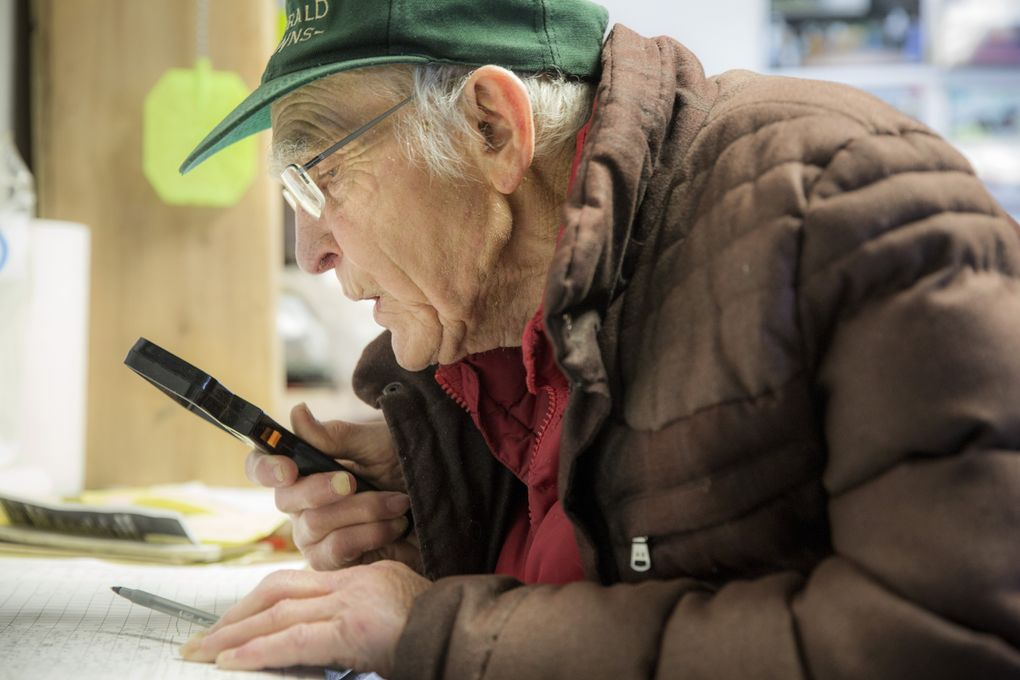 """Don Munger, 93, goes over his charts with a magnifying glass in his office in the stables at Emerald Downs – he is one of three horse trainers there in their 90s. Munger is a World War II vet who fought on Iwo Jima. """"It keeps me going, these horses,"""" said Munger. (Bettina Hansen/The Seattle Times)"""