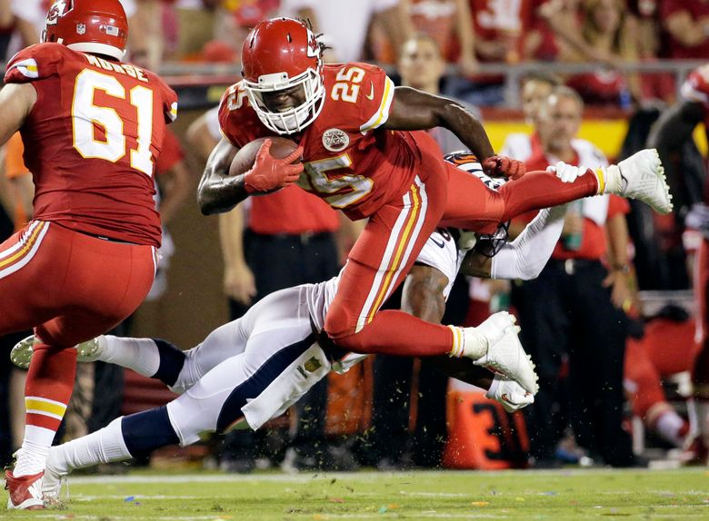 In this Sept. 17, 2015, file photo, Kansas City Chiefs running back Jamaal Charles (25) is tackled by Denver Broncos cornerback Chris Harris Jr., rear, during the second half of an NFL football game in Kansas City, Mo. Adrian Peterson and Jamaal Charles, both stalwarts for their previous clubs and with All-Pro credentials, are out there. But how many 30-plus running backs get long-term deals, even proven ones such as these? And both will want big bucks. (AP Photo/Charlie Riedel, File)