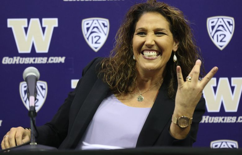 """University of Washington's new women's basketball coach Jody Wynn show she can flash the """"W"""" at her news conference, Monday, April 17, 2017, in Seattle."""