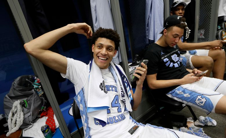 FILE – In this April 4, 2017, file photo, North Carolina forward Justin Jackson talks on his cell phone in the locker room after the championship game against Gonzaga at the Final Four NCAA college basketball tournament, in Glendale, Ariz. The school said Thursday, April 13, 2017, that Jackson will enter the NBA draft as a junior and hire an agent. (AP Photo/Mark Humphrey, File)