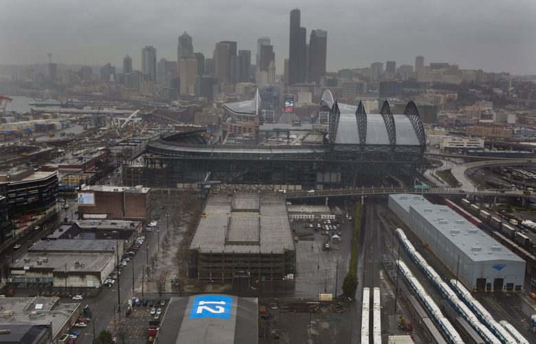 """In 2014 a """"12"""" flag was painted on the roof of a building at the site of the proposed arena for NBA and NHL use in Seattle's Sodo District.  (Ellen M. Banner/The Seattle Times)"""