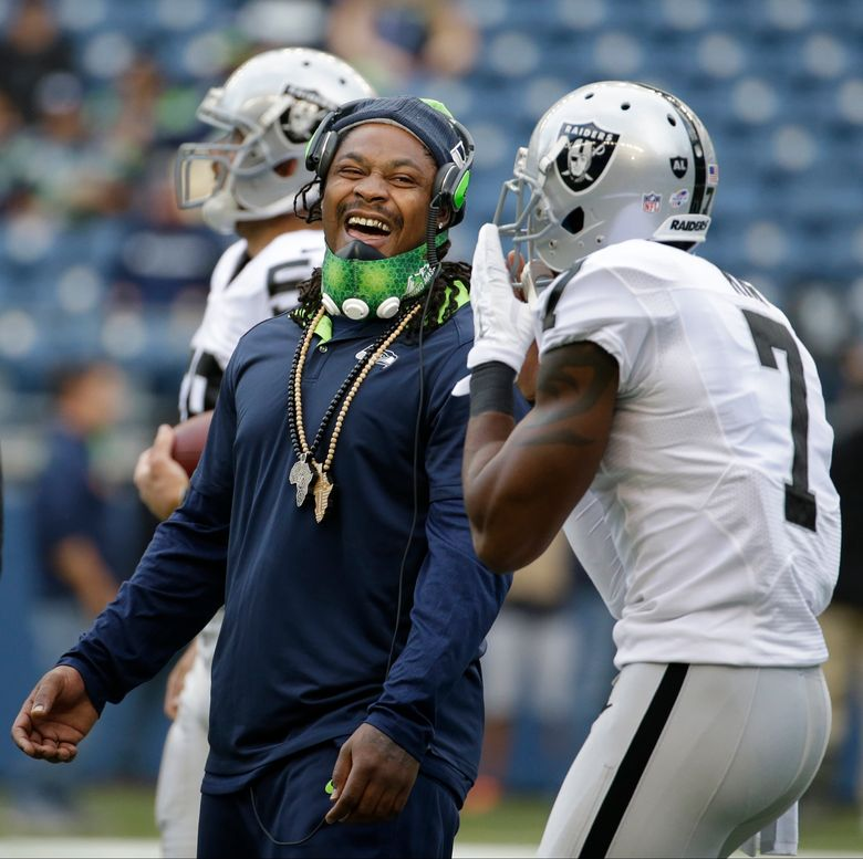 Seattle Seahawks running back Marshawn Lynch, left, talks with Oakland Raiders punter Marquette King before a preseason NFL football game, Thursday, Sept. 3, 2015, in Seattle. (AP Photo/Elaine Thompson)