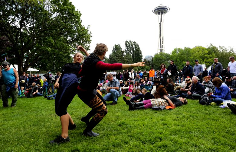 Katie Allen, left, and Carey French move to the music of Sarah Gerritsen and the Shadow Catchers at the 2016 Northwest Folklife Festival. (Alan Berner/The Seattle Times)