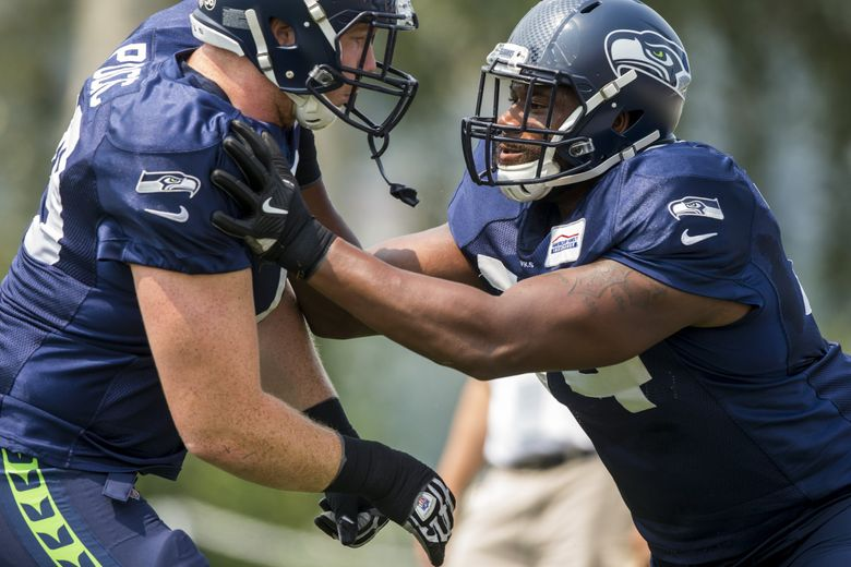 Seahawks center Ethan Pocic and offensive tackle George Fant, right, square off at Seattle Seahawks Training Camp.  (Bettina Hansen / The Seattle Times)