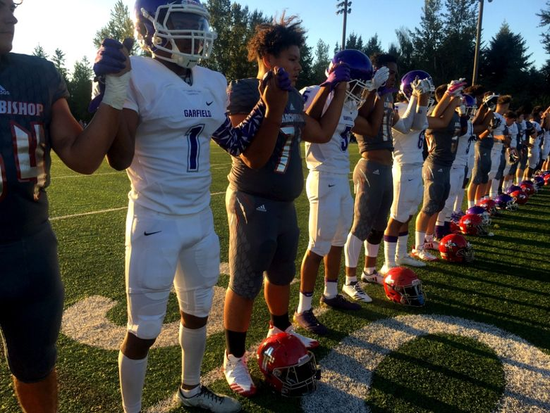 In a show of unity, Archbishop Murphy and Garfield players hold hands with arms raised during the national anthem Thursday night.  (Heather Graf / king5.com)