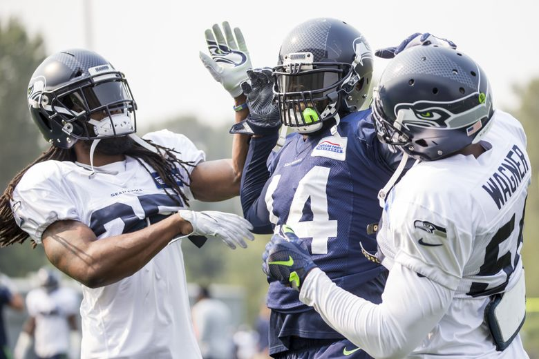 Seahawks cornerback Richard Sherman, left, and linebacker Bobby Wagner, right, pretend to gang up on fullback Marcel Reece during training camp Sunday. (Bettina Hansen/The Seattle Times)
