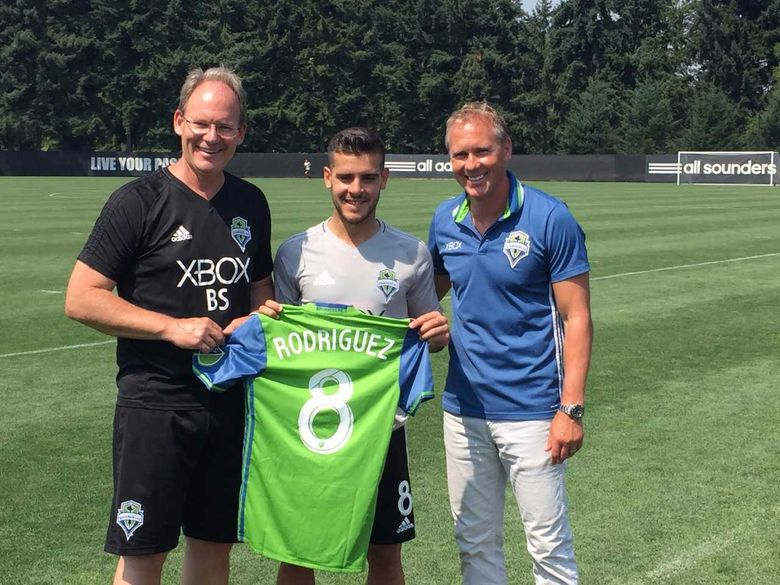 Newest Sounders midfielder Victor Rodriguez is flanked by coach Brian Schmetzer (L) and team vice president and sporting director Chris Henderson (R) on Tuesday at team's traning site in Tukwila. (Geoff Baker/Seattle Times)