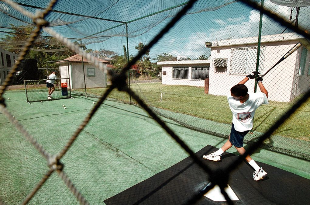 Edgar Martinez's house in the Maguayo sector of the Town of Dorado, Puerto Rico is pictured in 2001. Karlos Rivera, cousin of Edgar, during batting practice in the backyard of his house. (Juan Luis Martinez / Special for The Seattle Times)