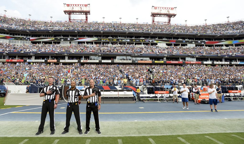 Officials stand on the sideline of the Seattle Seahawks during the playing of the national anthem before an NFL football game between the Seahawks and the Tennessee Titans Sunday, Sept. 24, 2017, in Nashville, Tenn. Neither team came out onto the field for the anthem. (Mark Zaleski / The Associated Press)