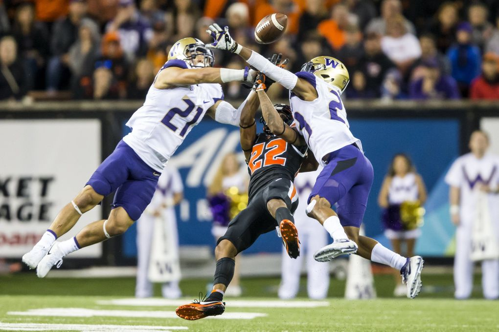 Washington defensive backs Taylor Rapp, left, and Jordan Miller, right, break up a pass intended for Oregon State wide receiver Seth Collins as the University of Washington Huskies take on the Oregon State Beavers at Reser Stadium in Corvallis, Oregon Saturday. (Bettina Hansen / The Seattle Times)