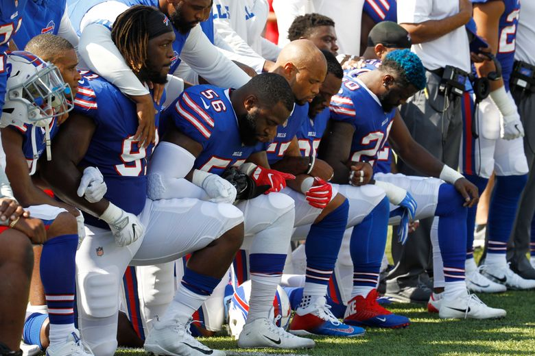 Buffalo Bills players take a knee during the national anthem prior to an NFL football game against the Denver Broncos on Sunday. (Jeffrey T. Barnes/AP)