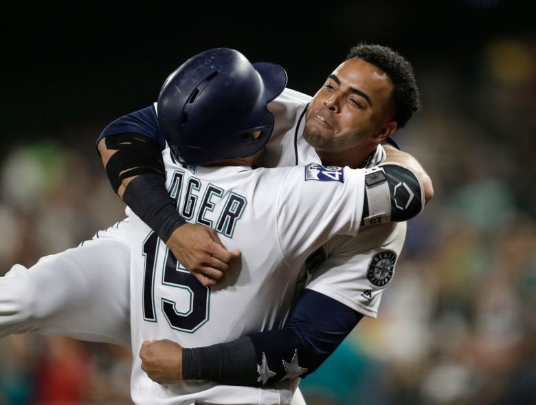 Nelson Cruz hugs Kyle Seager after Seager hit a solo home run against the Astros on Wednesday. (John Froschauer/AP)