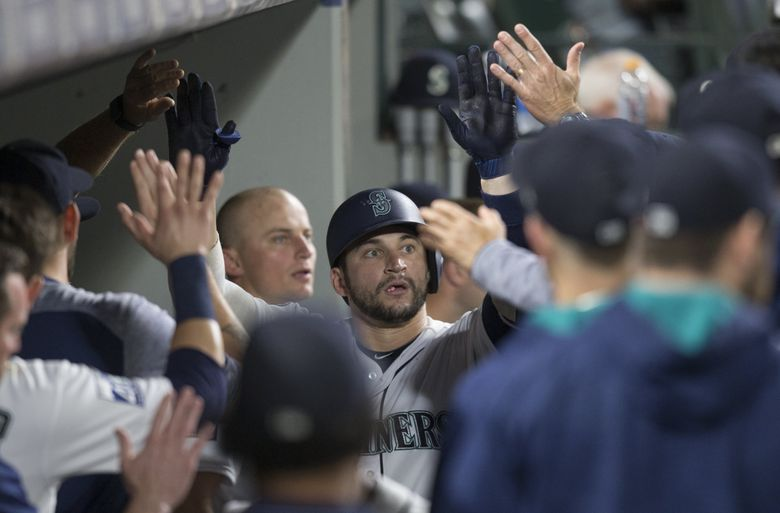 Seattle Mariners' Mike Zunino is congratulated by teammates in the dugout after hitting a solo home run off Oakland Athletics relief pitcher Chris Hatcher during the eighth inning of a baseball game Saturday in Seattle. (Stephen Brashear / The Associated Press)