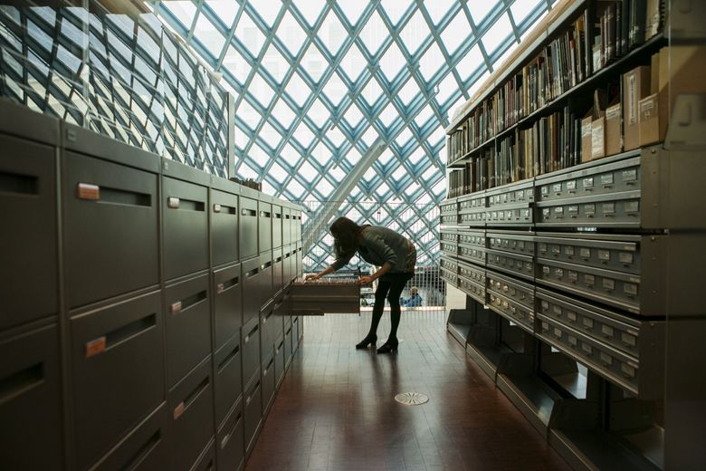 Ann Ferguson, the curator of the Seattle Collection, looks up a series of old news articles at Seattle Public Library's Central Library — a center of literary life in the city. (Bettina Hansen / The Seattle Times)