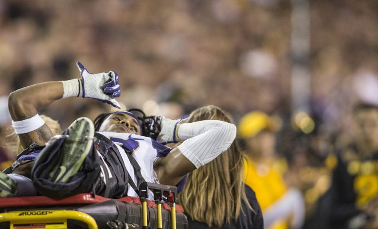 Huskies defensive back Jordan Miller is carried off the field after an injury as the University of Washington Huskies take on the Arizona State Sun Devils at Sun Devil Stadium on Saturday, October 14, 2017.  (Johanna Huckeba / Special to The Seattle Times)