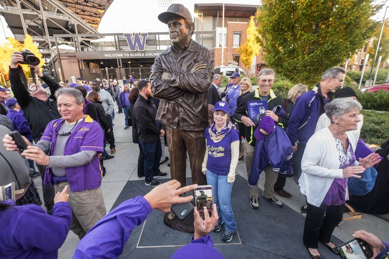 Huskies fans pose next to the statue of Don James unveiled Friday outside Husky Stadium. His widow, Carol, along with more than a dozen members of the extended family, former players and coaches, were on hand for the event.  (Dean Rutz/The Seattle Times)