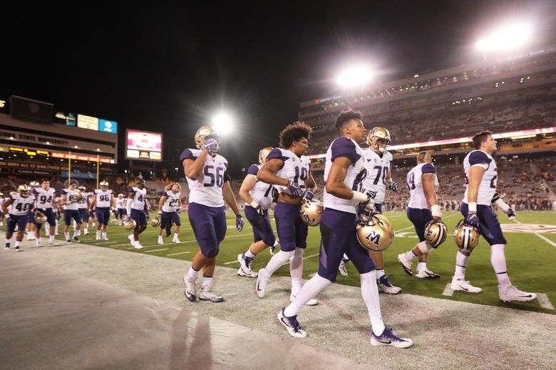 The Huskies finish their warmups before a night game in Tempe, Arizona, last month. (Bettina Hansen/The Seattle Times)