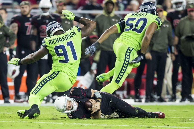 Cardinals quarterback Drew Stanton slides, narrowly missing Seahawks defensive tackle Sheldon Richardson and outside linebacker K.J. Wright.  (Bettina Hansen / The Seattle Times)