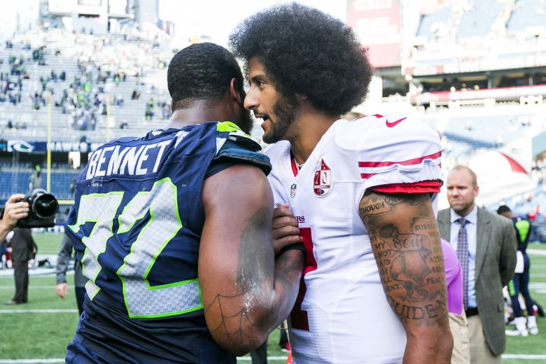 Seahawks defensive end Michael Bennett and San Francisco 49ers quarterback Colin Kaepernick talk after a game at CenturyLink Field on Sept. 25, 2016. Kaepernick had first knelt in protest during the national anthem a month earlier, in the exhibition season. He became a free agent after last season, and was not signed before the 2017 season. He has filed a collusion suit against the NFL. (Bettina Hansen/The Seattle Times)