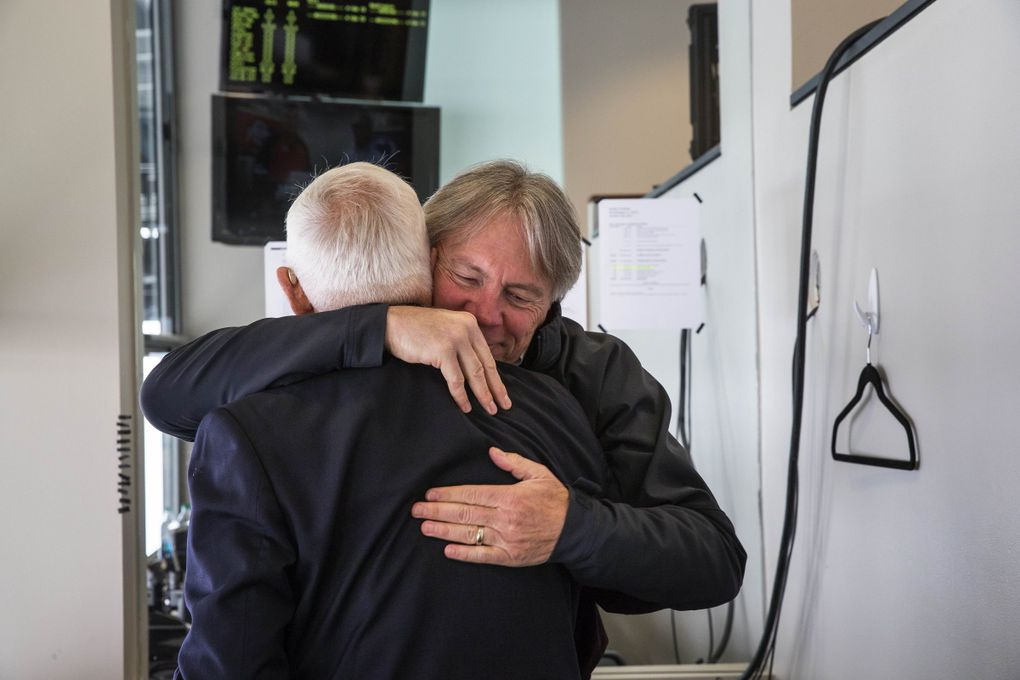 Bod Rondeau gets a warm hug goodbye from former Washington Athletic Director Mike Lude who came to see him in the broadcast booth.  (Dean Rutz / The Seattle Times)