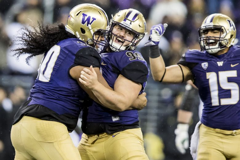 Huskies defensive linemen Vita Vea, left, and Greg Gaines celebrate a Gaines tackle for loss last season. With Gaines leading the way, the Husky defensive line is doing just fine without Vea this season.(Bettina Hansen / The Seattle Times)