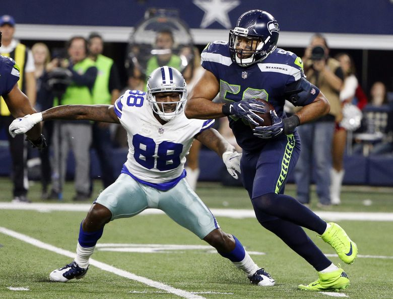 Seahawks linebacker K.J. Wright picks off a pass intended for Cowboys wide receiver Dez Bryant in a game last season. (Michael Ainsworth / The Associated Press)
