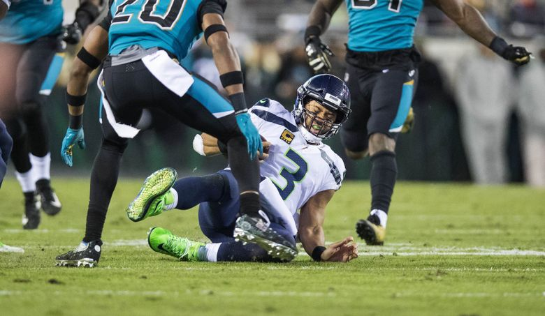Russell Wilson slides to the 35 and a first down in the 4th quarter. (Dean Rutz/The Seattle Times)