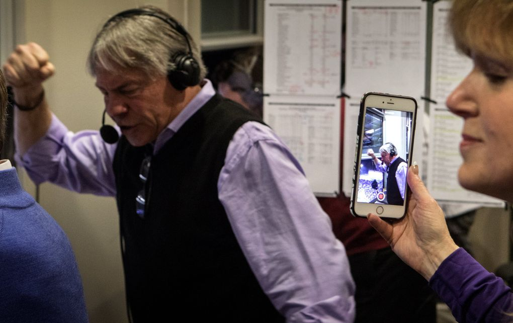 Molly Rondeau, wife of Bob Rondeau, shoots a video of her husband as he calls the first UW touchdown of the 110th Apple Cup.  (Ellen M. Banner / The Seattle Times)