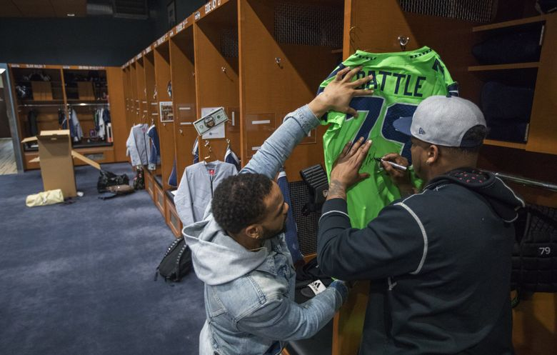Isaiah Battle signs a jersey for Thomas Rawls as the Seahawks players pack up their lockers  on Monday. (Steve Ringman / The Seattle Times)
