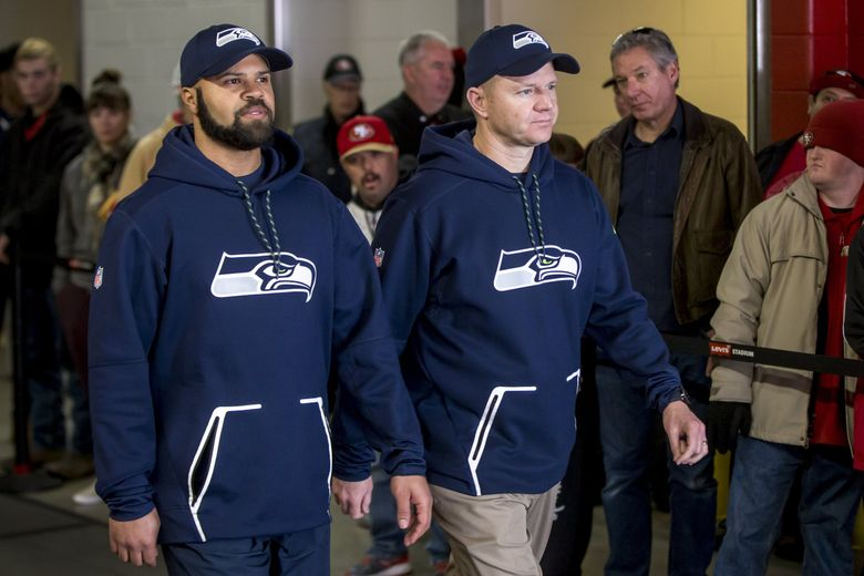 Defensive and offensive coordinators Kris Richard, left, and Darrell Bevell walked out together before the Seattle Seahawks take on the San Francisco 49ers at Levi Stadium in Santa Clara, California on Sunday, January 1, 2017. (Bettina Hansen / The Seattle Times)