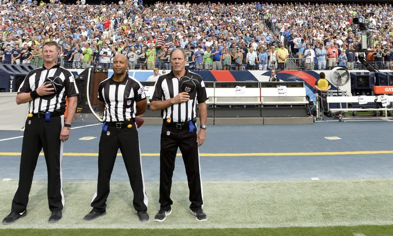 Officials stand on the sideline of the Seattle Seahawks during the playing of the national anthem before an NFL game between the Seahawks and Titans on Sunday, Sept. 24, 2017, in Nashville, Tenn. Neither team came out onto the field for the anthem. (Mark Zaleski/AP)